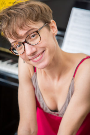 Skinny nerdy girl with short hair displays her unshaved snizz on piano bench
